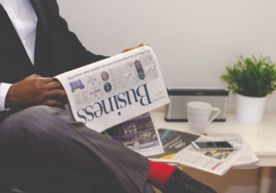 Business news: a man reading the business section of a newspaper